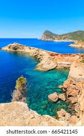 Sea cove with boat hosues in Punta Galera bay, Ibiza island, Spain