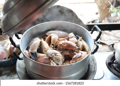 Sea Crabs cooking in silver pot hot steam with smoke
