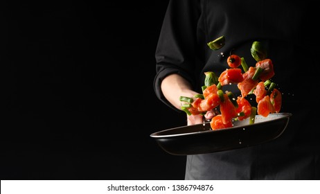 Sea cuisine, Professional cook prepares pieces of red fish, salmon, trout with vegetables.Cooking seafood, healthy vegetarian food and food on a dark background. Horizontal view. Banner