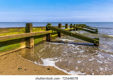 A sea defense groyne on Skegness beach, UK in summer with a wind farm just visible on the horizon.