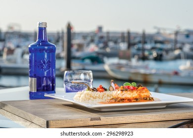 Sea dish grilled fish steak in gravy with vegetables and mushrooms with fried rice lying on a wooden board. Dish is on the table outside on the pier fish steak in gravy with vegetables and mushrooms