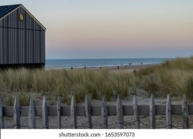 Sea evening landscape with a lonely beach, with dunes and a house on the shore against a beautiful sunset over the sea in Egmond aan Zee, Netherlands.
