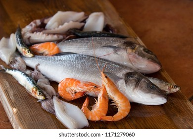 sea fish, prawns and calamari on wooden mat