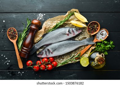 Sea fish seabass. Seafood on a black stone background. Top view. Free copy space.