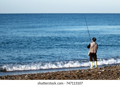 at sea, fishing with a fishing rod from the shore