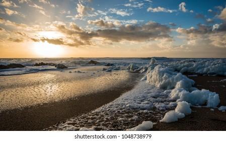 Sea foam  on the beach at sunset