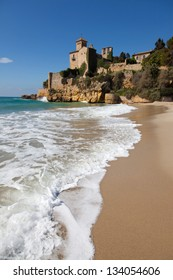 Sea foam on the beach of Tamarit with the castle in the background, Tarragona province, Catalonia.