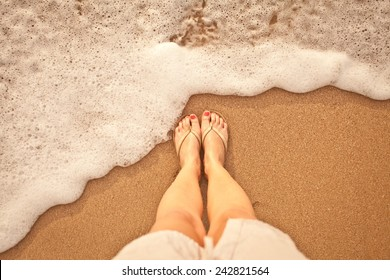 Sea foam, waves and naked feet on a sand beach. Holidays, relax, nature.