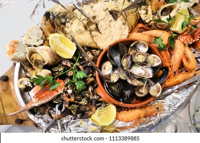 Sea food plate in Portugal - grilled mix of crab, shrimps, snails, goose barnacles (percebes) and clams.