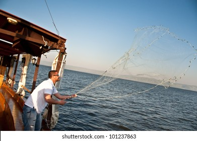 SEA OF GALILEE, ISRAEL - MARCH 22: An Israeli boat pilot demonstrates casting a fishing net on the Sea of Galilee, Israel, March 22, 2012.