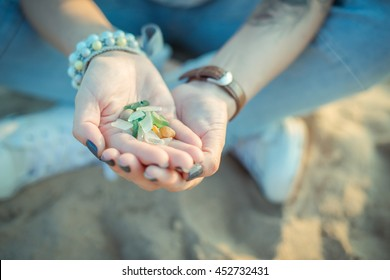 Sea glass pieces in the hands of a young woman