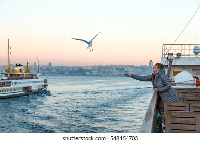 Sea Gull flying following passenger Vessels and young Woman watching its flight staying on board of Boat traveling across Bosporus channel in Istanbul city