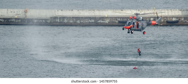 SEA HELICOPTER AND FROGMAN - Naval rescue machine over the breakwater of the sea port