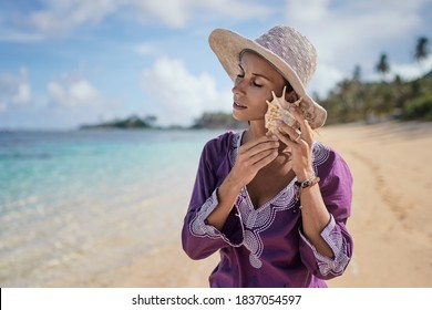 Sea in her hands. Close up of young woman holding big shell on the beach.