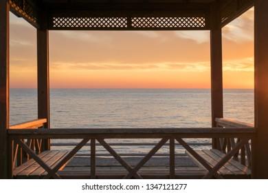 Sea horizon. Sunset view through gazebo on the beach.
