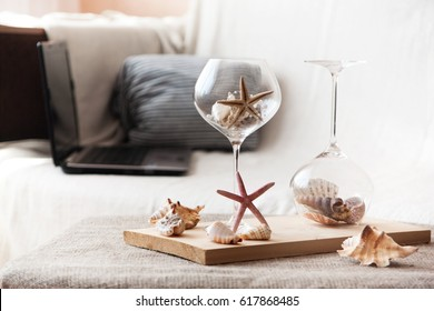 Sea interior, sea shells and stars on a wooden table in a larger glass.Detail of living room.
