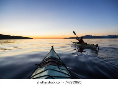 Sea kayaking in the ocean during a colorful and vibrant sunset. Taken in Jericho, Vancouver, British Columbia, Canada.