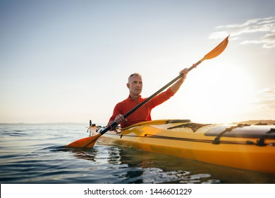 Sea kayaking. Senior man paddling kayak on the sunset sea. Acitve vacation, kayaking, paddling, canoeing