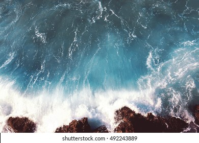 Sea landscape background, water with waves and rock, soft colors dramatic photo