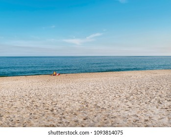 Sea landscape and elderly couple sitting on the sand