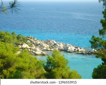 Sea landscape in Greece with green trees, white rocks and blue sea