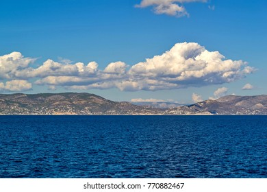 sea landscape with hills on the horizon and the blue sky with big white clouds