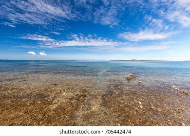 Sea landscape with islands on background, rocky shoreline with shallow water, Croatia, Europe.