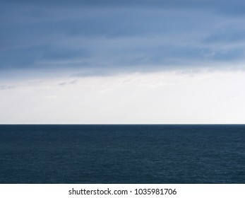 Sea landscape with layers of leaden clouds, clear skies and the Black Sea in Sochi, Russia