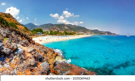 Sea landscape of the Mediterranean on clear sunny day. Sandy beach, rocks, blue sky, mountains and sea. Paradise Bay in Alanya. Tropical resort for summer holidays. coastline of sea resort beach