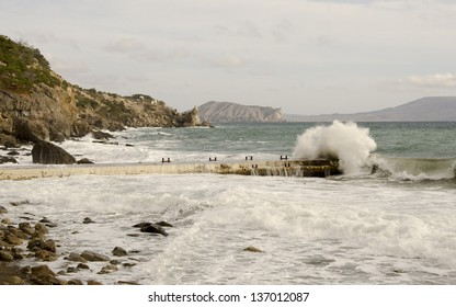 Sea landscape with mountain views, a dam and a big wave.