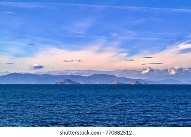 sea landscape with mountains on the horizon and the blue sky with clouds
