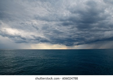 Sea landscape with rainy clouds and dark water. Cloudy sky background. Rainy weather with heavy clouds.