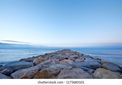 Sea landscape of a rocky pier going deep into skyline in the morning light before sunrise