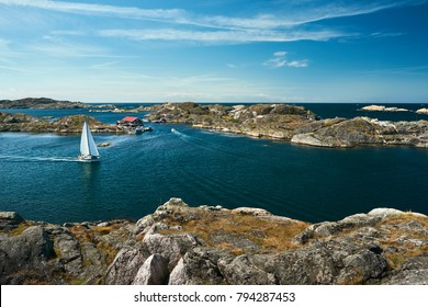 Sea landscape with sailboat and rocky coastline on the South of Sweden. Southern coastline of Sweden with view at sailing-ships and rocky islands.