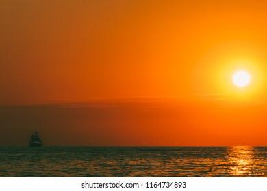 a sea landscape with a setting sun and a sailboat