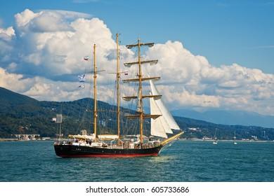 Sea landscape. Tall ships near coast. Sailing vessels. Blue sky with clouds. Evening. Autumn. Tall ship race.