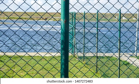 Sea landscape through metal fence gap. Iron fence and blurred lake scenery background. Coastline or shoreline behind a fence. Freedom concept.