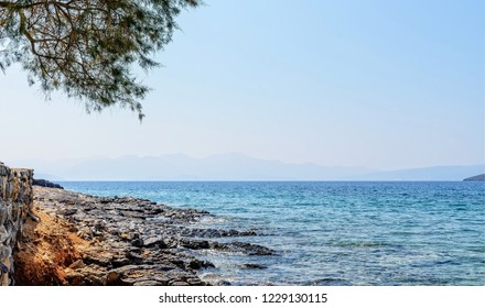The sea laps against the rocks in the bay at Elounda in Crete.  Distant hills can be seen over the horizon  and a blue sky is overhead.