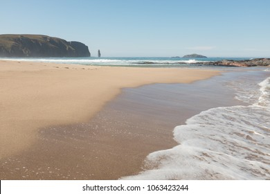 The sea laps the beach at Sandwood Bay with a view to the sea cliff stack of Am Buachaille on the horizon, Scotland, UK.