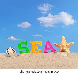 Sea letters on a beach sand against the blue sky