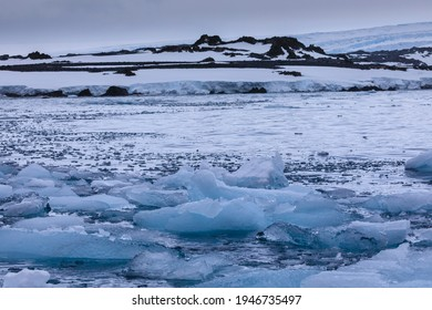 Sea level close up view of glacial blue sea ice on the surface of the icy sea off the Antarctic coast with a background of Antarctic scenery of a glacial Antarctica landscape