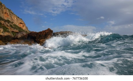 Sea level photo of huge waves reaching tropical volcanic seascape
