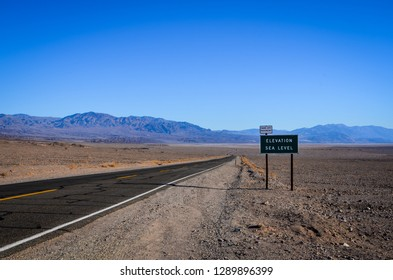 Sea level sign at long and curved road in death valley, nevada, united states