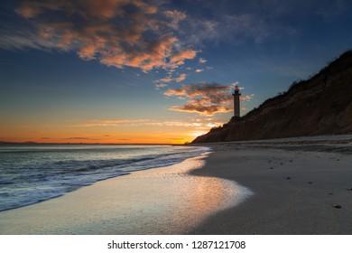 Sea lighthouse on the rocks at sunset