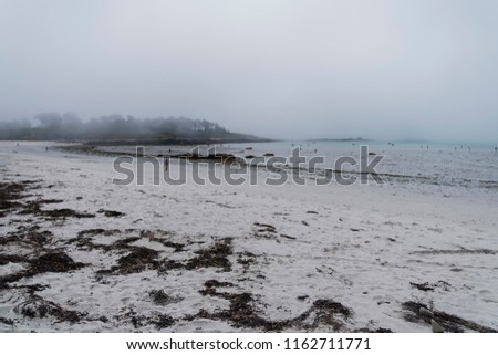 Sea mist descends on a beach in Landeda, Brittany. In the distance Children are playing in the sea.