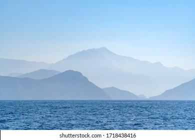 Sea and mountain view on a misty day. Blue degradation with copy space