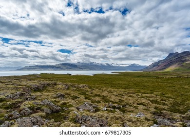 The sea and mountains under cloudy sky in Iceland