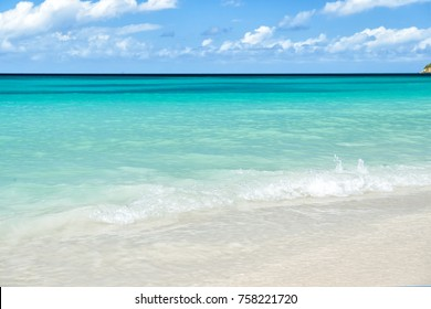 Sea or ocean beach with white sand, turquoise water waves in st johns, antigua. Seascape on sunny day on cloudy blue sky background. Summer, vacation, nature, beauty, paradise, freedom concept.