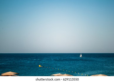 Sea panorama, overlooking the blue sea and beach with a yellow sun beds and umbrellas.