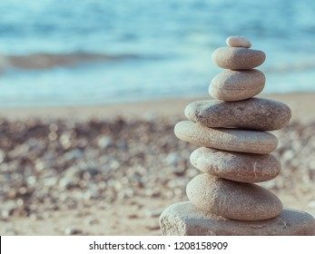 Sea pebbles tower closeup. Pebbles sculpture made on Barcelona beach. Beautiful soft background
